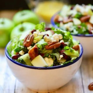 A large white bowl full of chopped salad topped with apples and pecans.