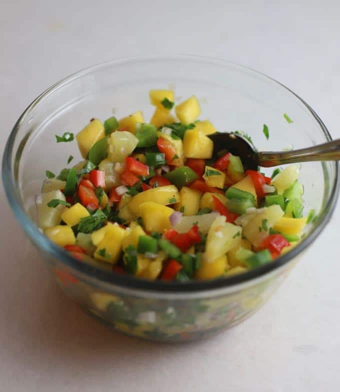 A clear glass bowl with mango salsa and a serving spoon.