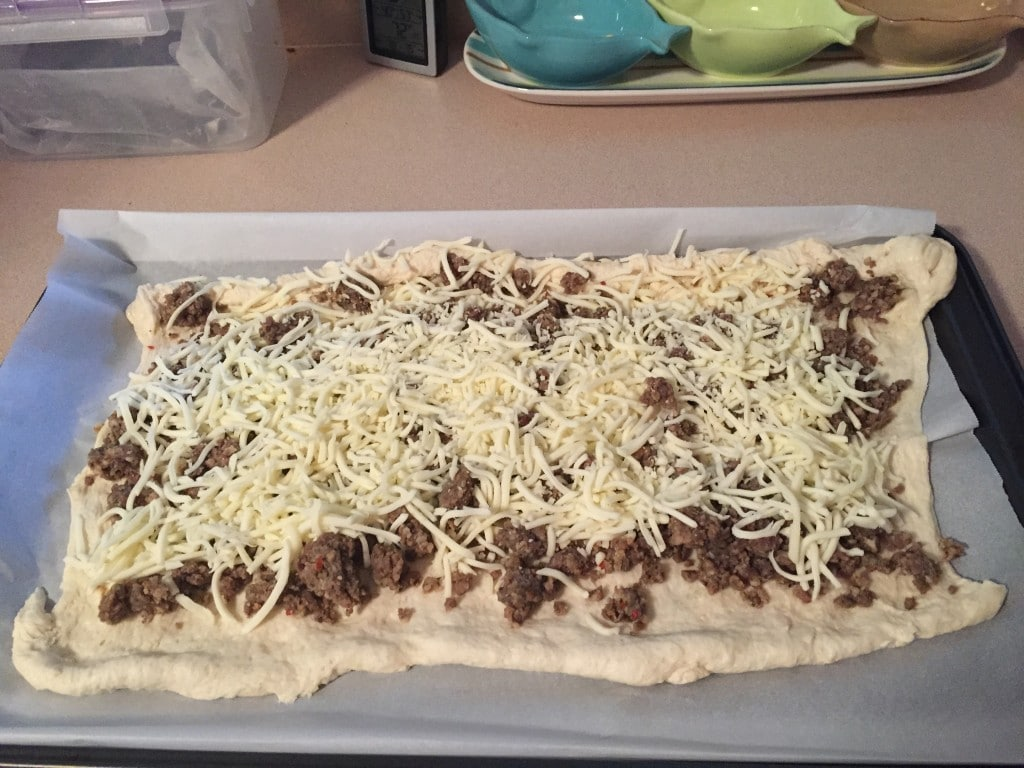 Dough on a baking sheet topped with meat and cheese.