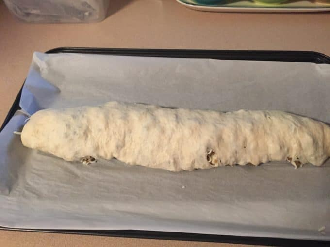 A baking sheet topped with parchment paper and a log of bread dough.
