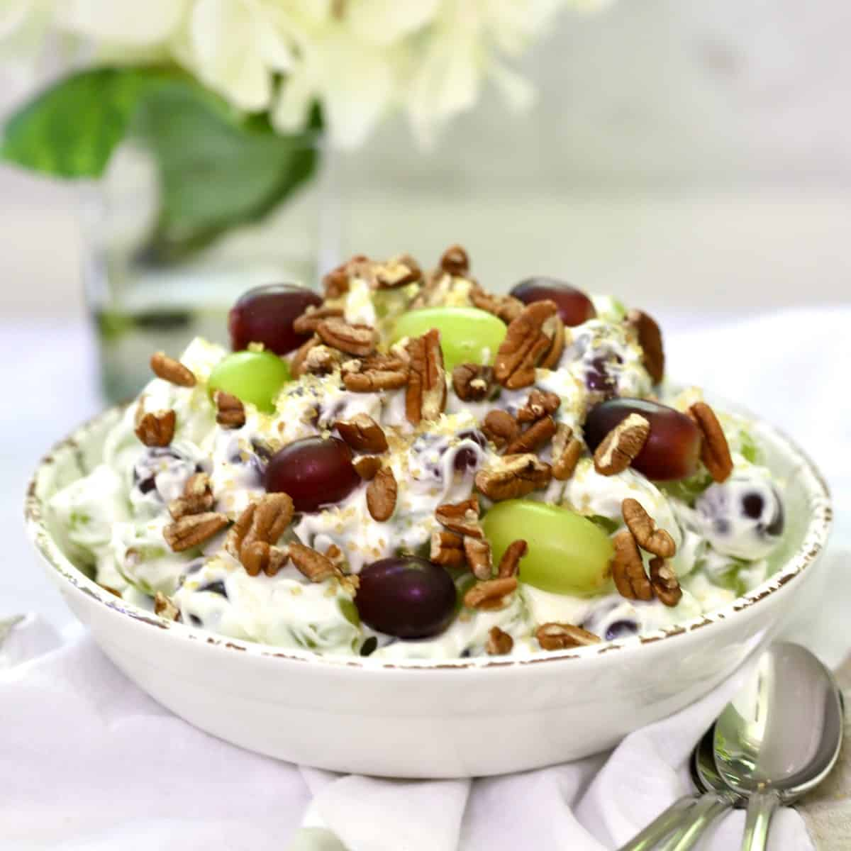 Easy Grape Salad with Cream Cheese in a white bowl garnished with pecans and with hydrangeas in the background
