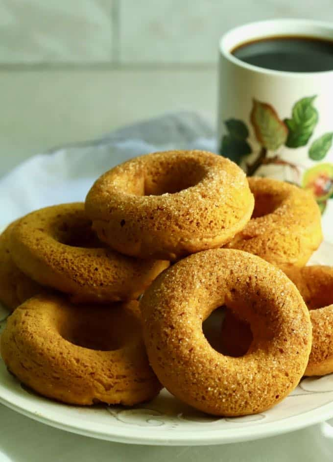 A white plate full of baked pumpkin donuts.