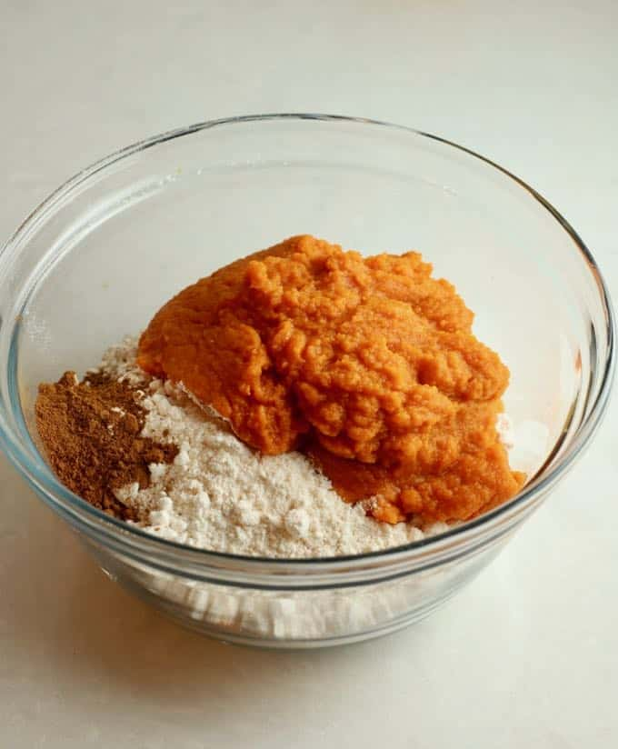 A clear glass bowl with pumpkin puree, yellow cake mix and pumpkin spice.