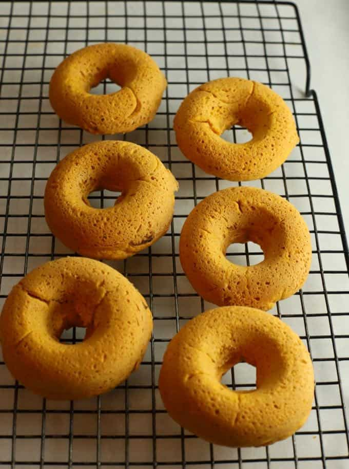 Pumpkin donuts cooling on a wire rack.