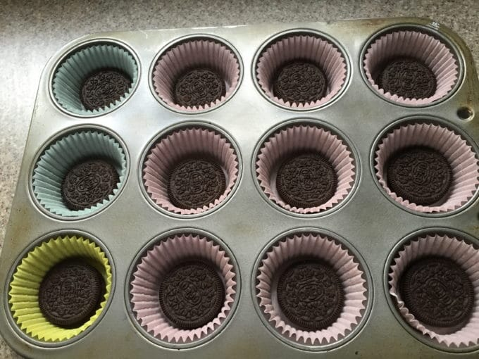 A muffin pan with paper liners and an Oreo at the bottom of each opening.
