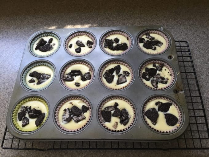 A muffin pan with a dozen Oreo Cheesecake Cupcakes topped with crumbled Oreos.