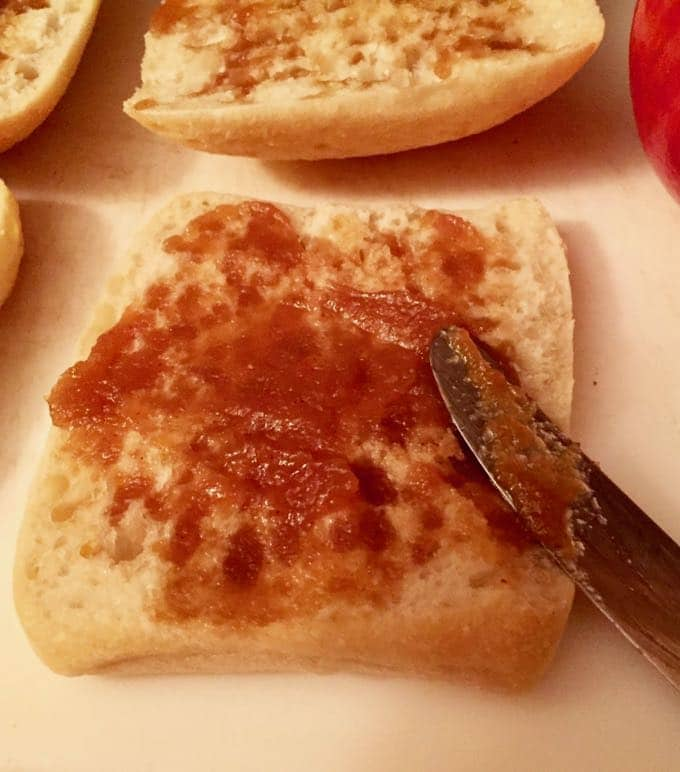 Spreading apple butter on rolls for the Ultimate Turkey Apple Brie Panini
