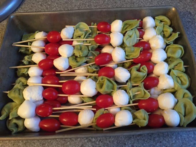 Make-Ahead Caprese Skewers with Pesto ready to be stored in the refrigerator until the party