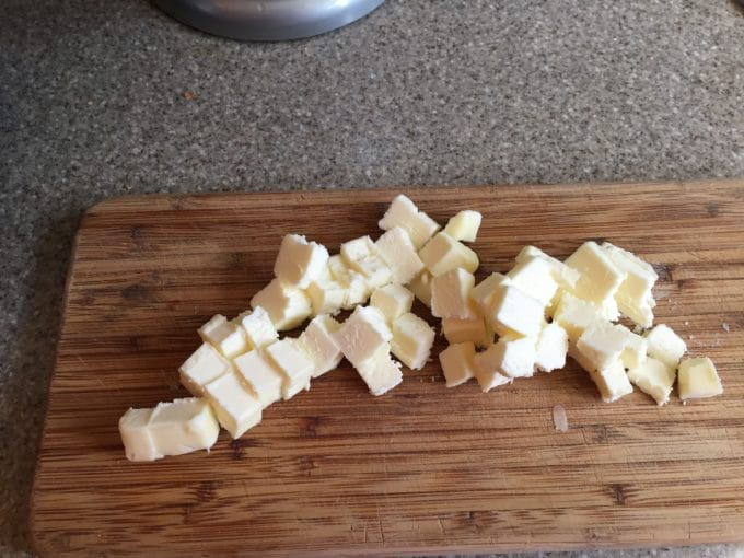 A stick of butter cut into small cubes on a cutting board.