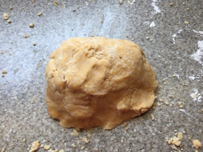 A ball of dough for making homemade Cheez-Its on a cutting board.