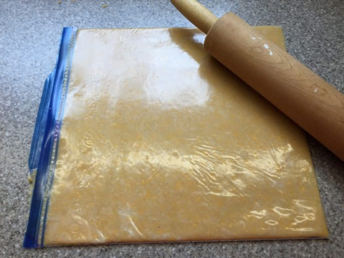 A Ziplock storage bag full of cheese cracker dough rolled flat with a rolling pin.