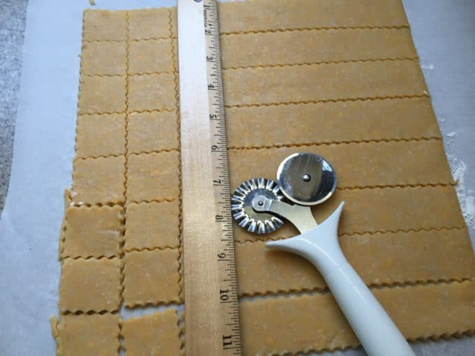 Cheese cracker dough being cut into small squares before baking.