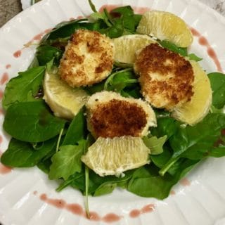 Arugula and Goat Cheese Salad on a white plate topped with orange slices.