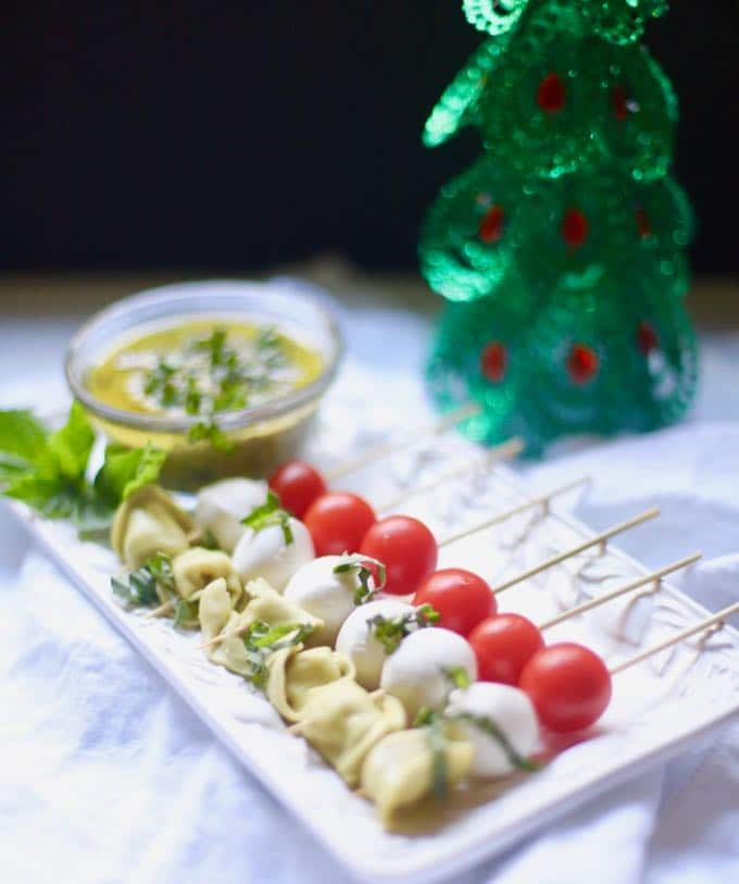 A white plate with skewers holding tortellini, fresh mozzarella balls, and cherry tomatoes.