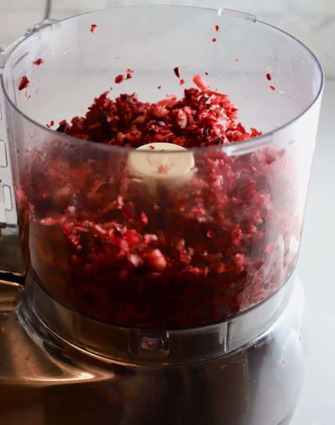 A food processor with coarsely chopped cranberries.