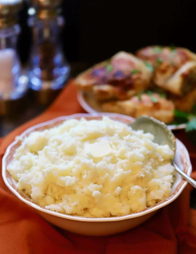 A serving bowl of Creamy Mashed Potatoes steaming hot and ready to serve.