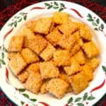 A plate of homemade cheez-it crackers on a Christmas plate.