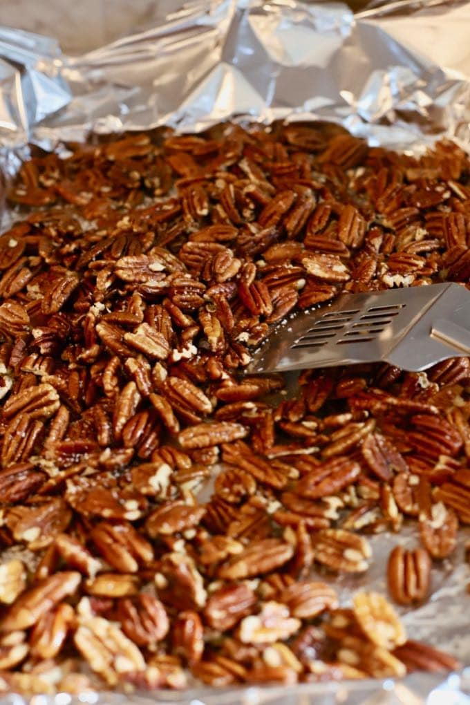 Pecans on a baking sheet being stirred to make roasted pecans.