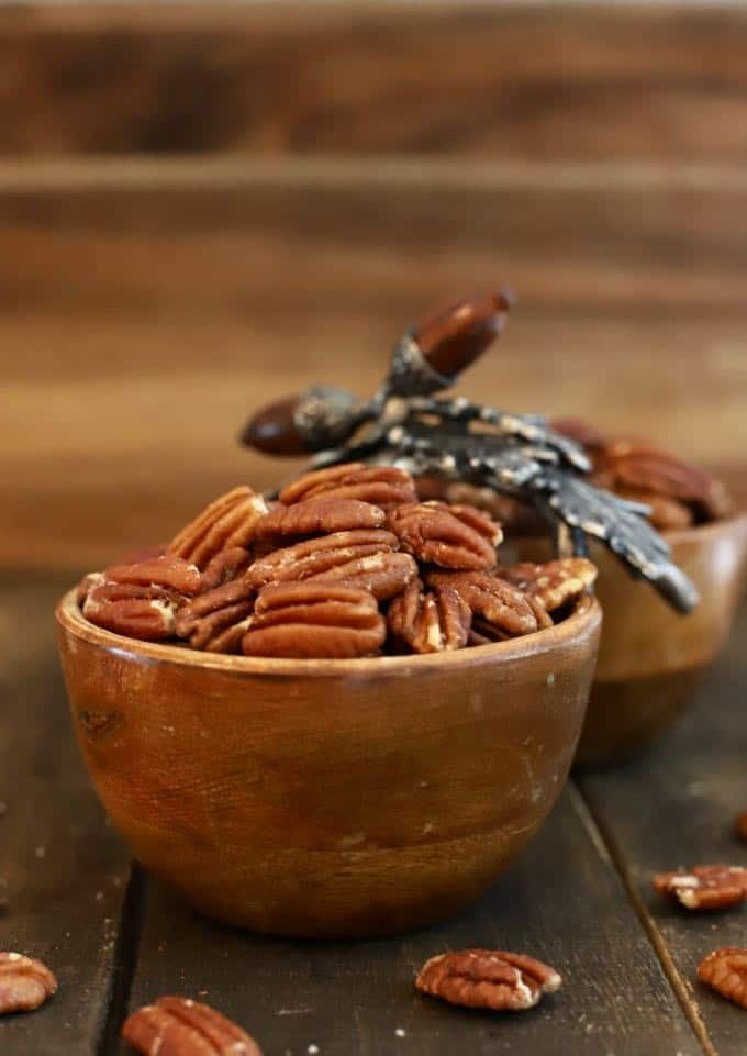 A wooden bowl on a wooden board full of roasted pecans.