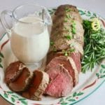 Sliced beef tenderloin on a Christmas platter garnished with parsley.