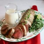 Roasted Beef Tenderloin with Onion Blue Cheese Sauce on a Christmas plate and red napkin.