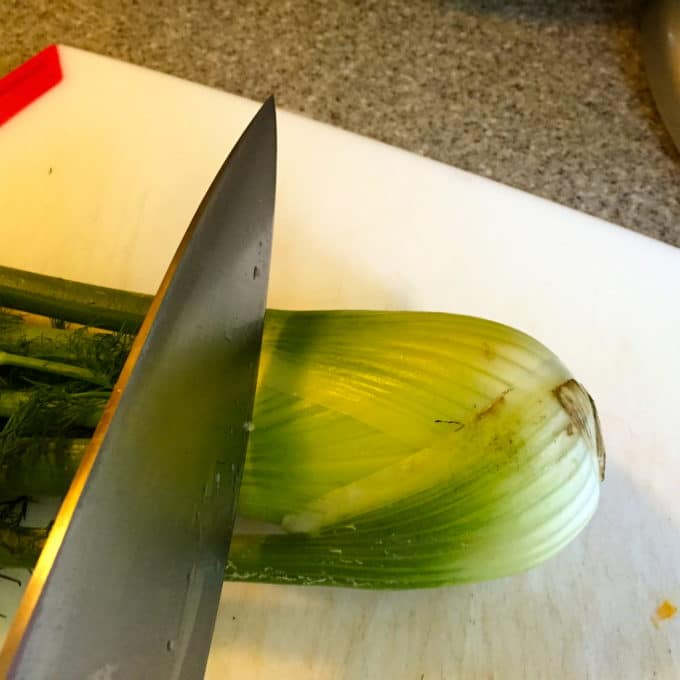 Using a kitchen knife to cut the fronds off fennel.
