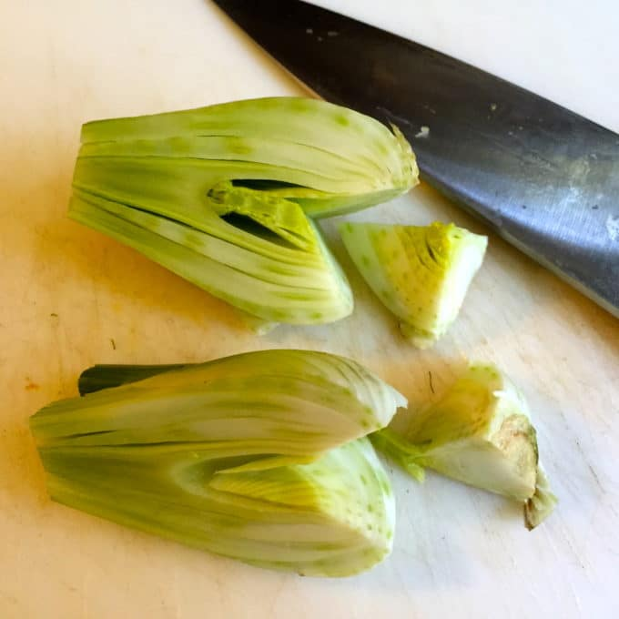 A fennel bulb sliced in half and cutting out the core with a knife.