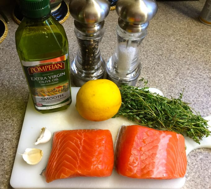 Two pieces of raw salmon, lemon, garlic, extra virgin olive oil, salt, pepper, and thyme on a cutting board.