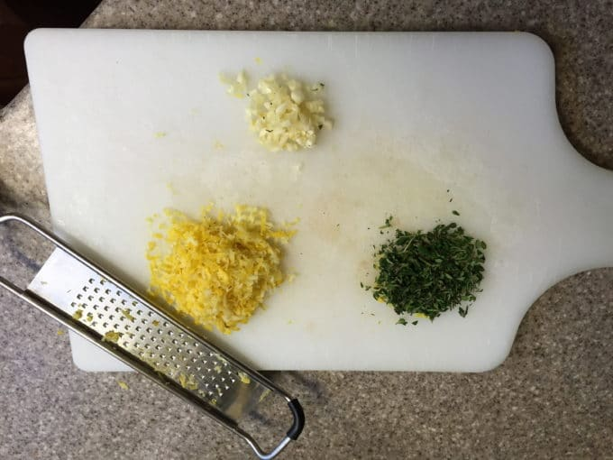 Finely chopped thyme, garlic and lemon zest on a cutting board along with a zester..