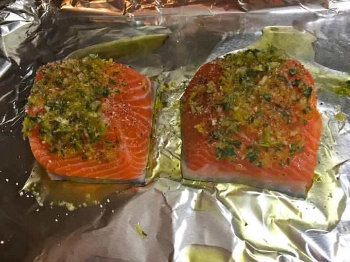 Two pieces of salmon topped with lemon herb mixture with salt and pepper on top of aluminum foil.