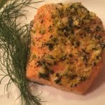 A piece of cooked salmon topped with herbs on a plate.