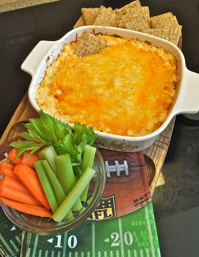 Buffalo chicken dip in a white dish with celery and carrot sticks.