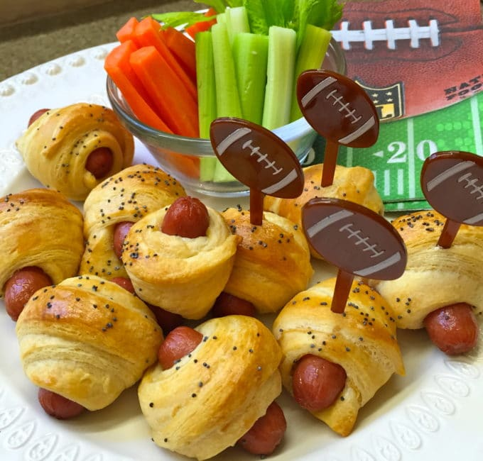 Pigs in a Blanket topped with poppy seeds with football plastic forks.
