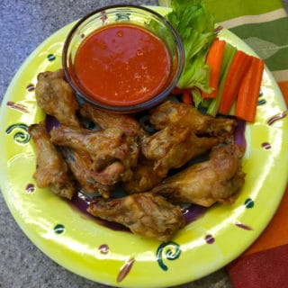Baked Buffalo Wings on a yellow plate with a small bowl of buffalo sauce on the side.