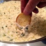 Dipping a toasted baguette slice into Easy Crab Mornay Dip