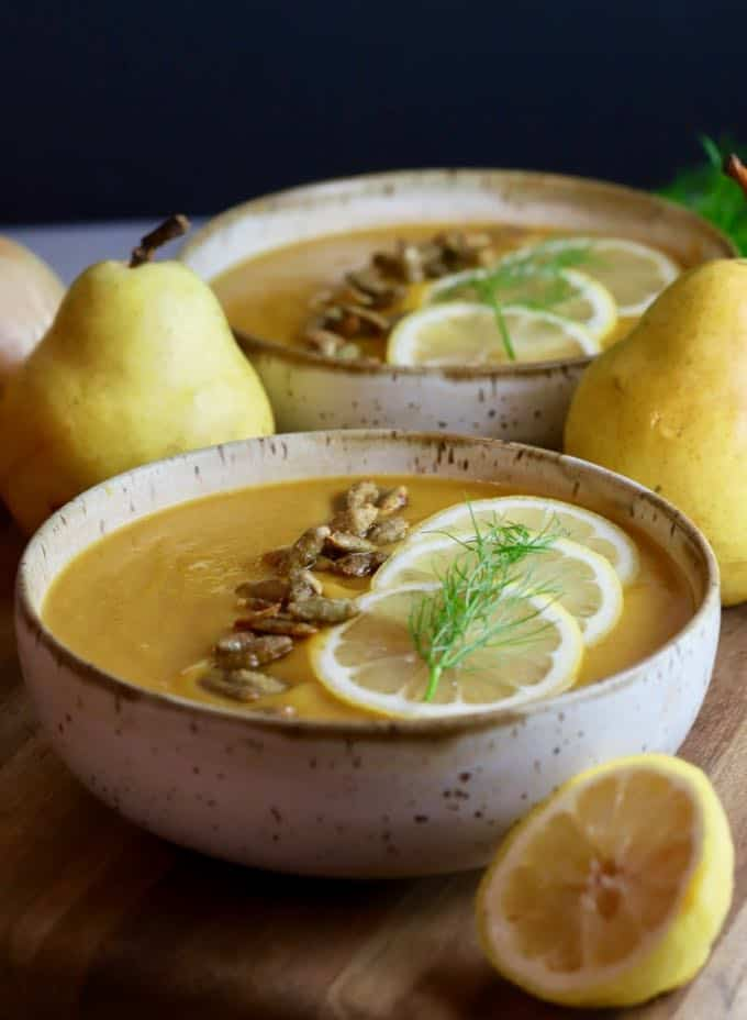 Two bowls of butternut pear squash soup topped with lemon slices and fennel.