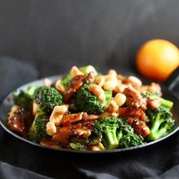 A small black skillet full of chicken and broccoli stir fry topped with cashews.