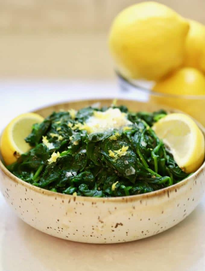 Sauteed Spinach with Lemon and Garlic in a bowl with a pat of melted butter on top.