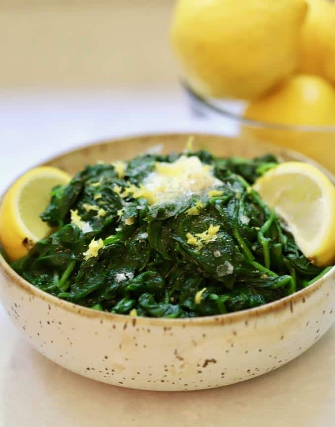 Sautéed Spinach with Lemon and Garlic garnished with lemons and butter