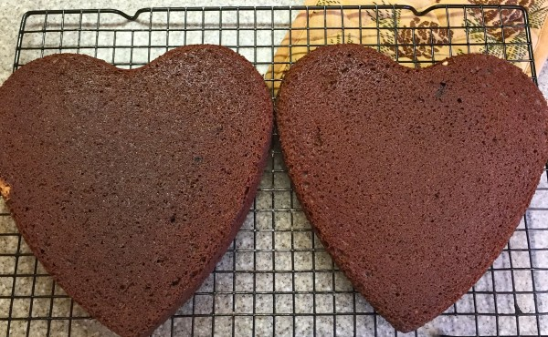 Two heart shaped chocolate cakes on a baking rack.