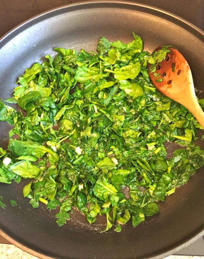 Cooking spinach in a skillet to make Oysters Rockefeller.