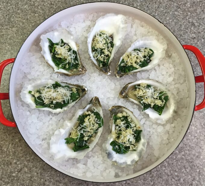 Uncooked oysters in their shells on a bed of salt in a skillet.