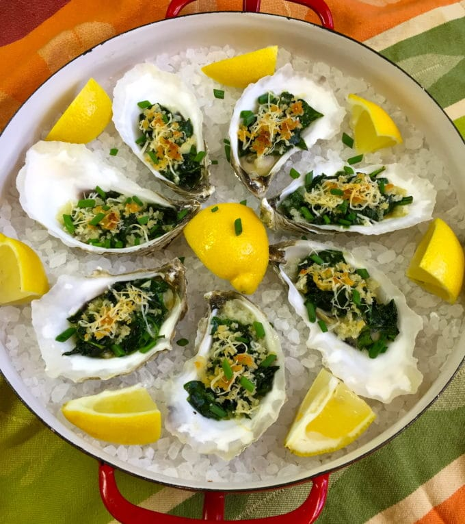 Oysters Rockefeller in their shells on a bed of rock salt, garnished with lemons.
