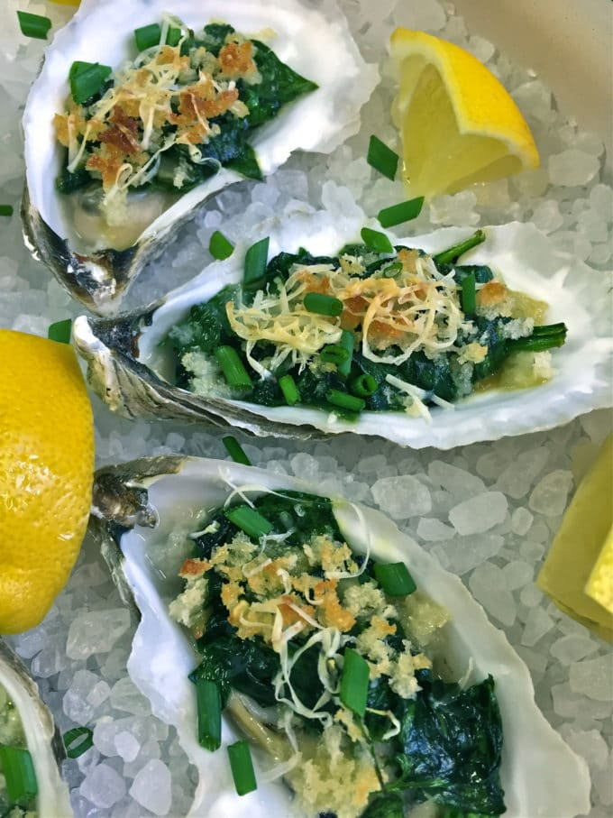 Oysters Rockefeller on a bed of rock salt garnished with lemons.