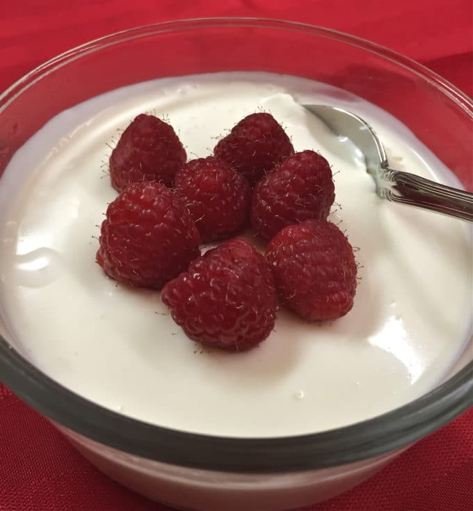 Raspberries and Cream Dessert in a clear bowl with a spoon
