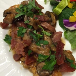 Chicken Marsala with Proscuitto and salad on a plate.