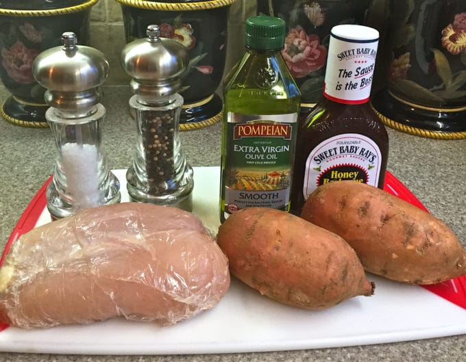 Chicken breasts, sweet potatoes, olive oil, BBQ sauce and salt, and pepper; ingredients for a chicken sheet pan dinner.