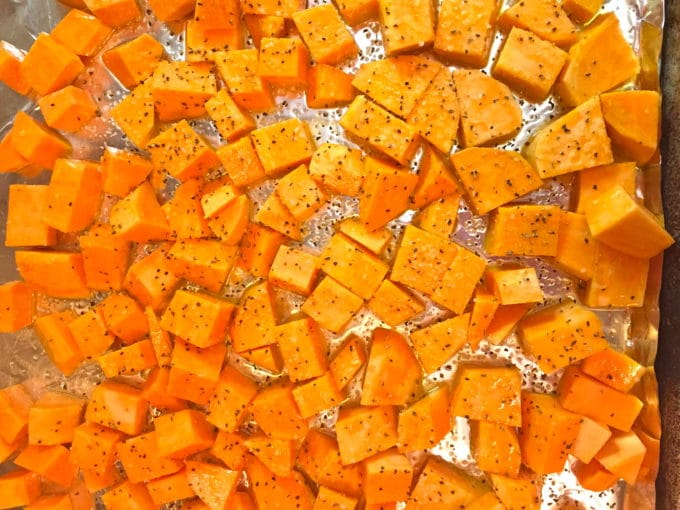 A layer of cubed sweet potatoes on a sheet pan ready for the oven.