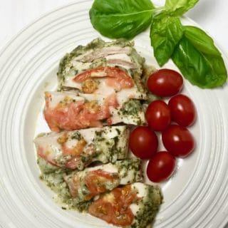 Basil Pesto Chicken on a plate garnished with basil and cherry tomatoes.