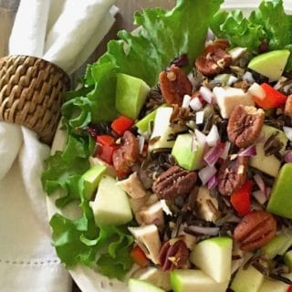 Healthy Wild Rice Chicken Salad on a bed of lettuce in a white serving bowl